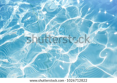 Blue water surface with bright sun light reflections, water in swimming pool background closeup #1026712822