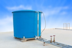 Blue water tank of industrial building on roof top or deck and blue cloud sky background