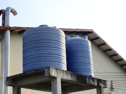 Blue water tank on the tower: plastic water tank installed on the back of the factory For storing water used in food production or reserving water for emergency use.