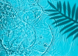 Blue water texture background on the noon sunlight with tropical leaves shadow.