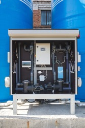 Blue water tower pump complex's switch box with a monitor, valves and buttons