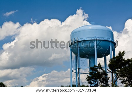 blue water tower under cloudy skies