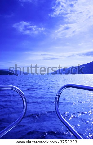 blue waterscape seen from a boat, focus on front waves, picture taken on Loch Ness, Scotland, UK