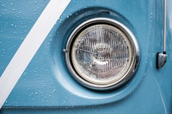 Blue wedding camper van rain on paint and round glass headlight with  H4 size bulb and shiny polished chrome surround, radio arial to the side and a strip of white ribbon visible