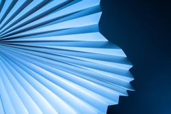 Blue-white three-dimensional background. Paper fan pattern on dark background. Geometric background with a three-dimensional cardboard object. Sometimes blurred abstract image.