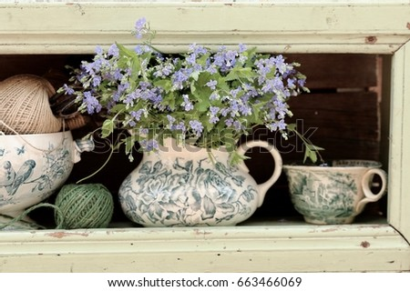Blue wild flowers in antique, vintage pitcher, big cup on very old aged, weathered wooden shabby chic mint color shelf