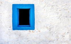Blue window on white wall of greek house