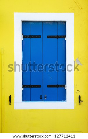 blue window shutters on a yellow colored house of Burano