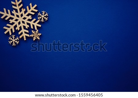Photo of Blue winter holiday background with handmade wooden snowflake.Paper backdrop with hand crafted snow flake figure made from rustic wood material.Christmas wallpaper with empty space for text