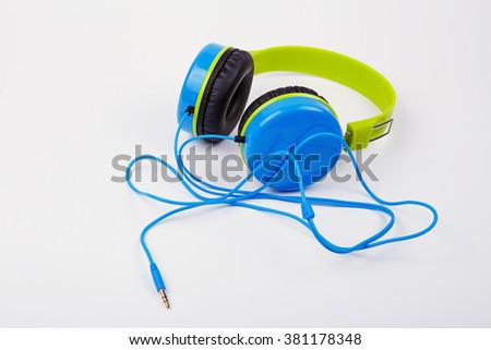 Blue with green Headphones on a white background. Bright colored headphones for children #381178348