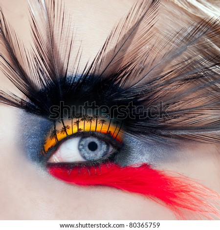 blue woman eye makeup bird inspired with black and red feathers and palm tree sunset in eyelid