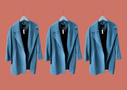 Blue women coat on hangers isolated on red background. Composition of clothes. Flat lay, top view, copy space. Ladies' Trench Coat. Winter clothes pattern. Strict classic brown coat