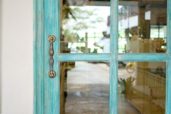 Blue wooden door and glass with steel hand lock at the entrance of restaurant.