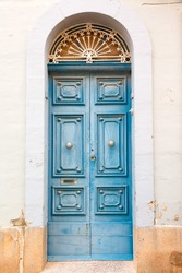 blue wooden front door to the house in the Mediterranean