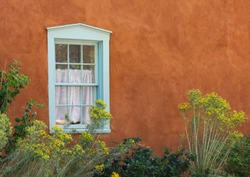 Blue wooden window in adobe stucco house. Pueblo adobe plaster architecture. Santa Fe, New Mexico, Southwest USA, United States of America. With white curtain and yellow plants