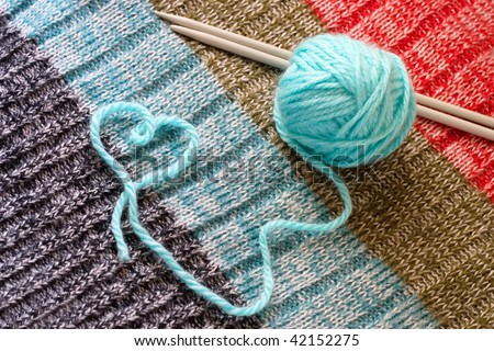 blue wool and knitting needles, thread in form of heart