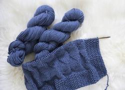 Blue wool knitting blanket in progress with yarn hank and needles