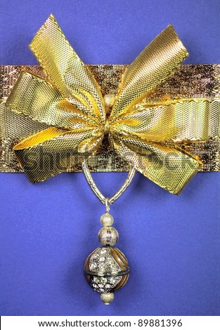 Blue wrapped gift with a golden bow and jewel