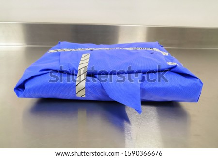 Blue Wrapped Sterile Surgical Instrument Set On Table