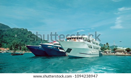 blue yachts and a white cruise at phiphi island, Thailand.