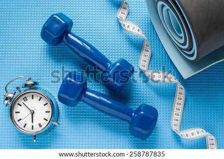 Blue yoga mat, two dumbbells, tape measure and alarm clock.