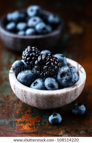 Blueberries and blackberries in small stone dishes