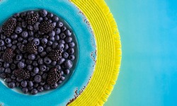 Blueberries and blackberries on a turquoise plate. Vibrant colourful background.