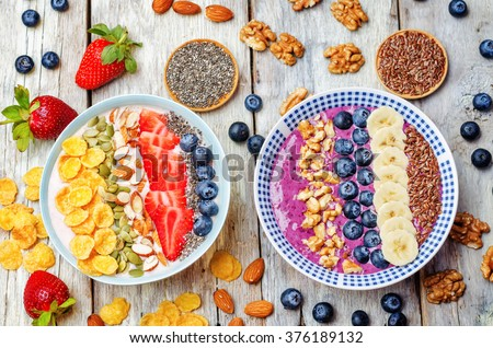 Blueberries and strawberries healthy smoothies breakfast bowls with nuts, seeds and fruits. toning. selective focus