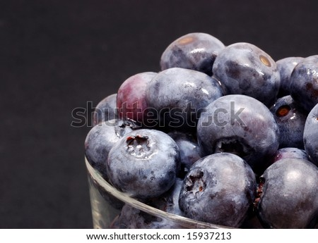 Blueberries in a bowl against a black background