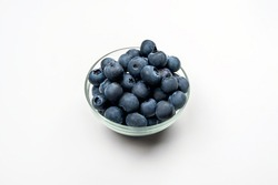 Blueberries in a glass Cup on a white background.