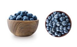 Blueberries in a wooden bowl. Ripe blueberries with copy space for text. Blueberry isolated on white. Bilberries  on a white background. Top view. Blueberries on a white background.