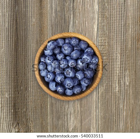 Blueberries in a wooden bowl. Top view. Ripe and tasty blueberries on a wooden background.