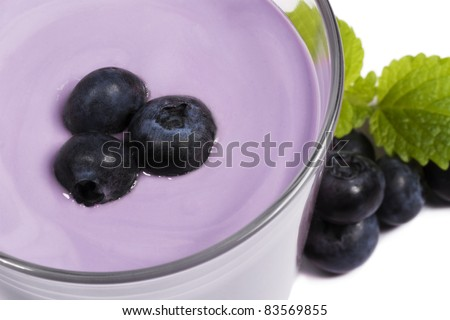 blueberries on top of a blueberry milkshake with blueberries and melissa aside on white background