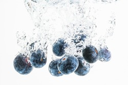 Blueberries sinking underwater with air bubbles isolated on white background. Berry fruit theme