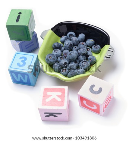 Blueberries with wooden blocks on white