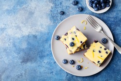 Blueberry cake, cheesecake on a plate. Blue stone background. Copy space. Top view.
