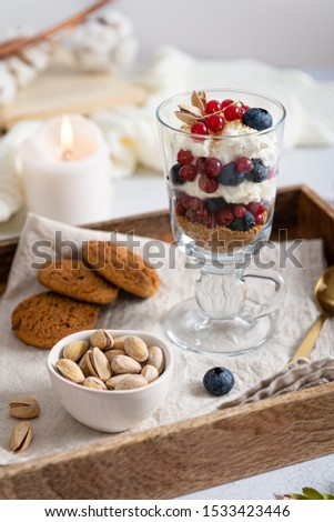 Blueberry dessert, cheesecake, trifle, mousse in a glass on a wooden tray with pistachios and oatmeal cookies. Side view. Cozy autumn composition. Confectionery.
