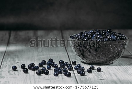 Blueberry in a glass bowl isolated on a dark background. Beautiful juicy berries in a deep plate. A bunch of ripe blueberries. Kitchenware design element. Abundant harvest. Copy space