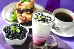 blueberry milkshake with fresh fruits in tall glass