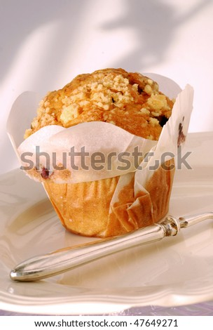 blueberry muffin on a slant with silver fork