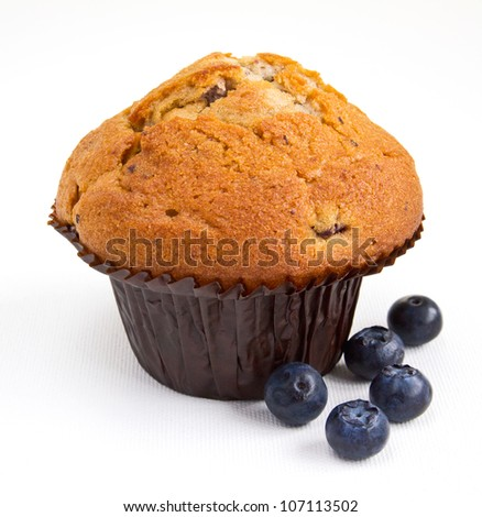 Blueberry muffin with fresh fruit on white background. Close up