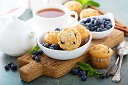 Blueberry muffins in a bowl with a cup of tea for breakfast