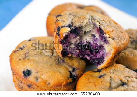 Blueberry Muffins on a wooden plate showing the berries inside