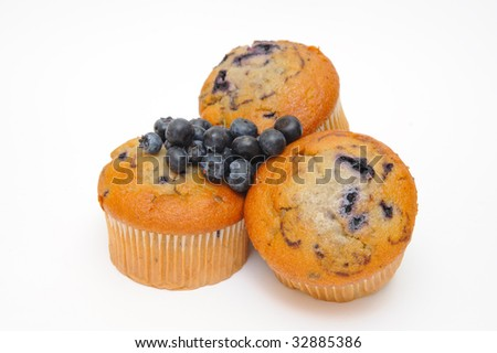 Blueberry muffins with fresh blueberries on top of the cakes on a light colored background.