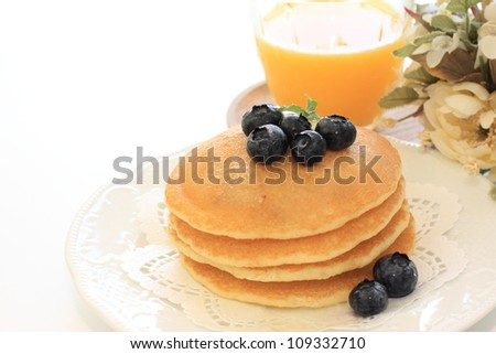 Blueberry pancake and orange juice for breakfast image