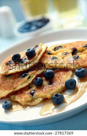 Blueberry pancakes with maple syrup.  An indulgent sweet breakfast.