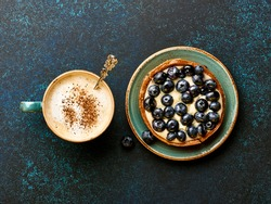 Blueberry tart with cup of coffee on blue stone background.