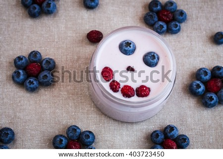 Blueberry yogurt with a smiling face. Kids breakfast of yogurt. Top view