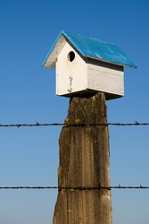 Bluebird box near Bickleton Washington with a classic blue roof on an old fence post against a blue sky background.  This area is known as the bluebird capital of the world.