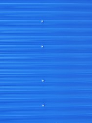 Blueish metallic corrugated sheet roof texture. Deep blue profiled sheet panel. Corrugated Metal Roof Exterior Close up.